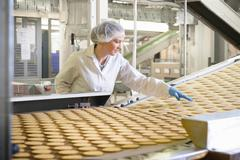 Biscuit factory worker inspecting freshly made biscuits on production line Stock Photos