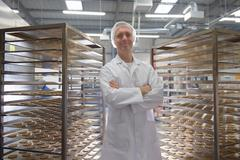 Portrait of baker with trays of freshly baked biscuits in food factory Stock Photos