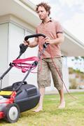 Man mowing green lawn Stock Photos
