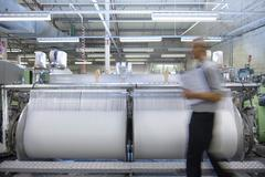 Worker passing threads and industrial loom in textile mill - stock photo