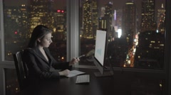 Businesswomen working on computer desk in office at night analyzing charts Stock Footage