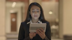 Young african american female searching the web on tablet in the city at night Stock Footage