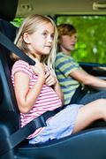 Girl sitting in car booster seat Stock Photos