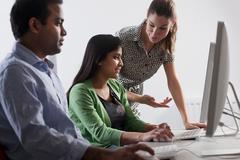 Teacher helping student use computer Stock Photos