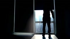silhouette of man in the morning starting daily business in city office building - stock footage