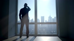 Silhouette of man in the morning starting daily business in city office building Stock Footage