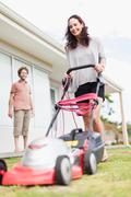 Woman mowing green lawn Stock Photos