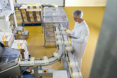 Worker inspecting packed products on conveyor belt in biscuit factory Kuvituskuvat