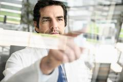 Doctor pointing to glass panel Stock Photos