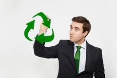 Businessman drawing recycle symbol in air Stock Photos