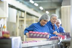 Workers on packing line in biscuit factory Kuvituskuvat