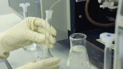 Chemist working with glass flask. Row of test tubes in medical laboratory Stock Footage