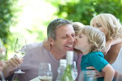 Boy kissing father at table outdoors - stock photo