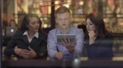 Diverse group of friends looking at a tablet computer talking together Stock Footage