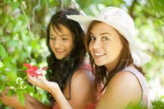 Women admiring flowers in park - stock photo