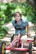 Boy riding go-kart on path Stock Photos