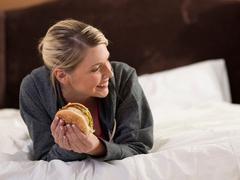 Woman eating hamburger on bed Stock Photos