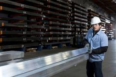 Worker holding metal in plant Stock Photos