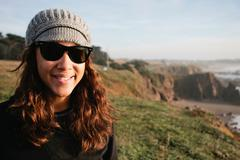 Smiling woman in sunglasses on cliff Stock Photos
