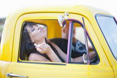 Woman fixing makeup in car mirror Kuvituskuvat