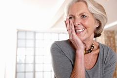 Smiling older woman gasping - stock photo