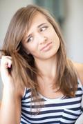 Teenage girl twirling her hair Stock Photos
