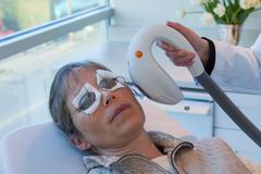 Doctor giving patient sunspot treatment - stock photo