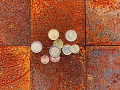 Euro coins on brick floor - stock photo