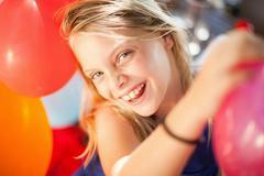 Smiling girl holding balloon at party Stock Photos