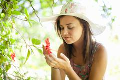 Woman admiring flower in park Stock Photos