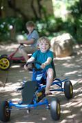 Boys riding go-kart on path Stock Photos