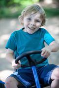 Boy riding go-kart outdoors Stock Photos