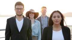 Diverse multi ethnic group of young friends having a fun time outdoors together Stock Footage