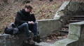 Teenager having troubles, sitting in park alone with bottle of alcoholic drink Footage