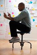 Man sitting on stool with digital tablet Stock Photos