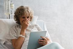 Female hospital patient with digital tablet, laughing Stock Photos