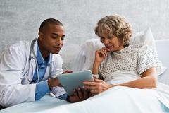 Doctor showing digital tablet to patient in hospital - stock photo