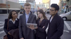 Multi ethnic group of young professional people talking together on city street Stock Footage