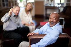 Older man smiling in armchair Stock Photos