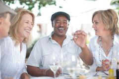 Older friends having wine together Stock Photos