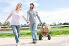 Parents pulling son in wagon Stock Photos