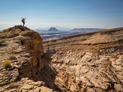 Hiker cheering on rocky hilltop Stock Photos