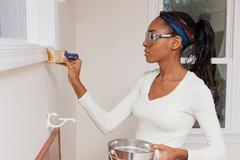 Woman painting trimming in new home - stock photo