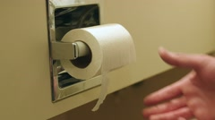 A man grabs toilet paper while using the bathroom in a hotel Stock Footage