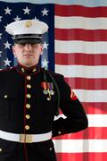 Serviceman in dress blues by US flag Stock Photos