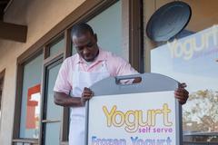 Man opening frozen yogurt store - stock photo