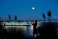 Woman taking picture of cruise ship Stock Photos