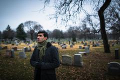 Man visiting graveyard - stock photo