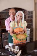 Older couple holding pie in kitchen Kuvituskuvat