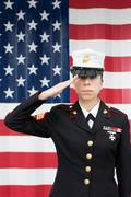 Servicewoman in dress blues by US flag Stock Photos